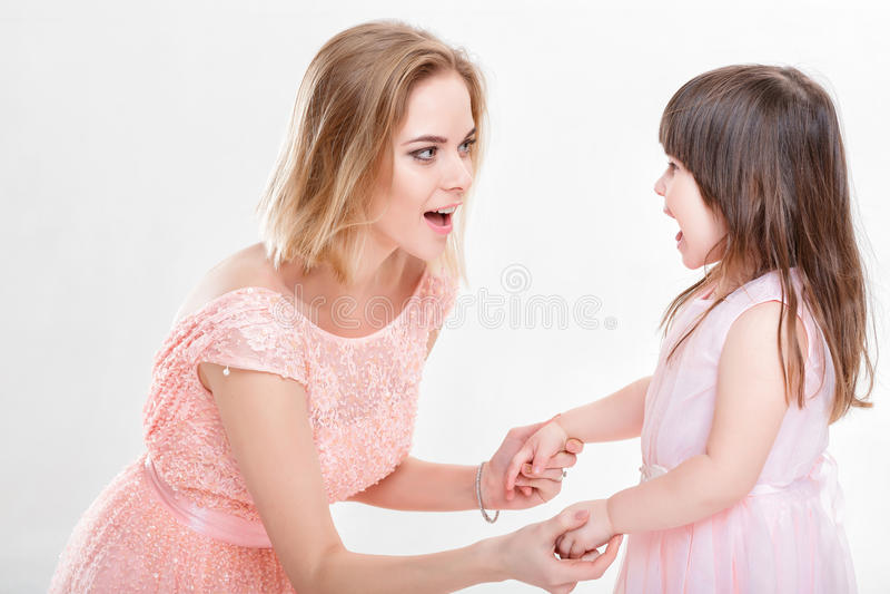 La maman blonde soulageant la fille dans le rose habille des princesses Bébé photo stock