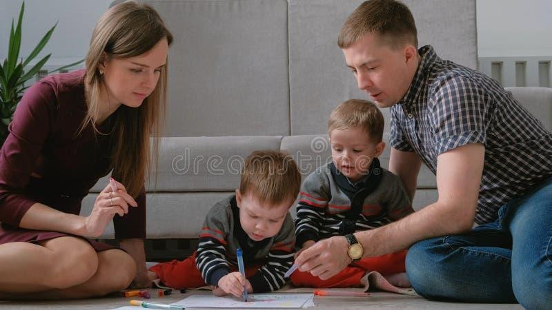 La maman de famille, le papa et deux frères jumeaux réunissent des marqueurs et ont senti des stylos se reposer sur le plancher images libres de droits
