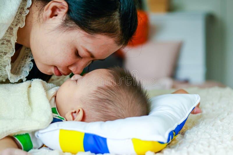 La maman embrasse le fils de bébé endormi photographie stock