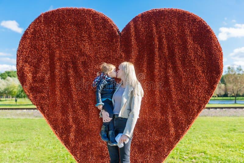 La maman embrasse sa fille la tenant dans des ses bras en parc de ville photos libres de droits