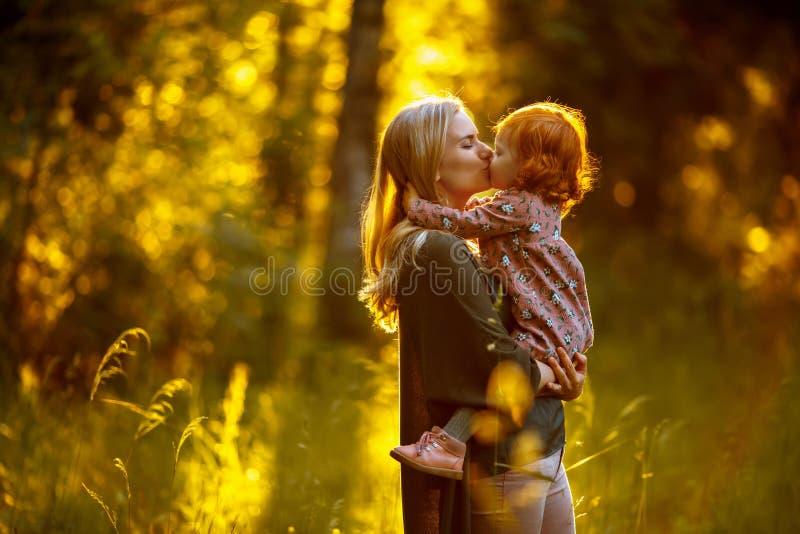 La maman embrasse son dérivé roux au coucher du soleil pendant l'été en Th photos stock