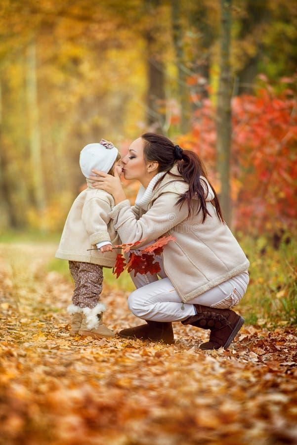 La maman embrasse une petite fille dans un bec, parc d'automne photo libre de droits