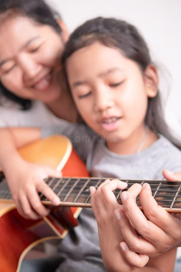 La maman enseigne sa fille à jouer la guitare avec bonheur photos libres de droits