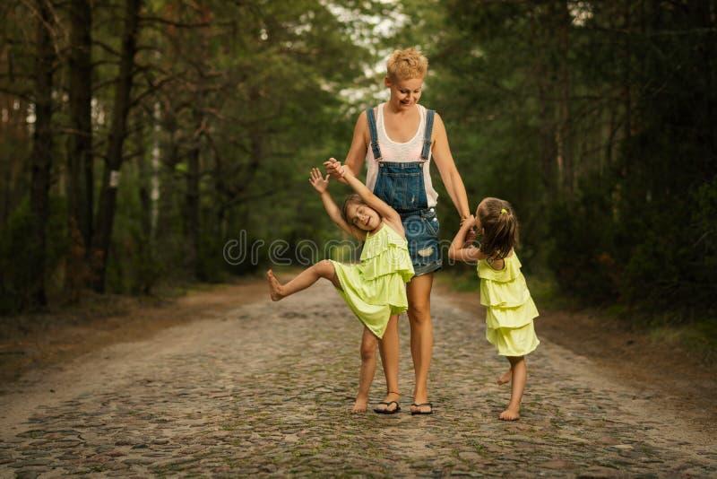 La maman et deux belles filles marchent le long du chemin dans les bois image stock