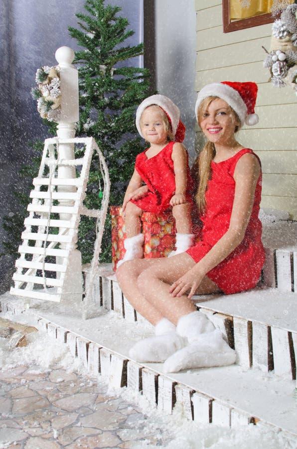 La maman et la fille dans des costumes de Noël s'asseyent sous la neige images stock