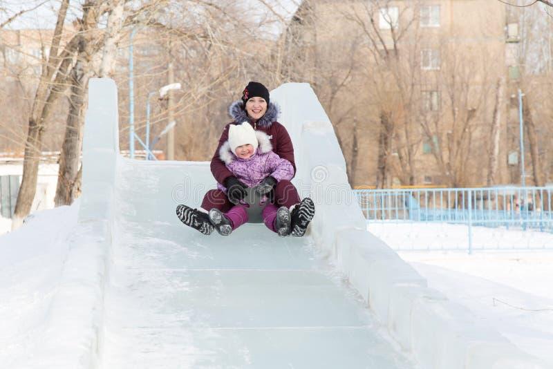 La maman et la fille montent d'une montagne neigeuse photo libre de droits