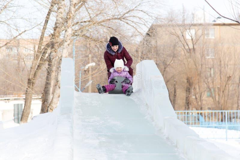 La maman et la fille montent d'une montagne neigeuse photographie stock libre de droits