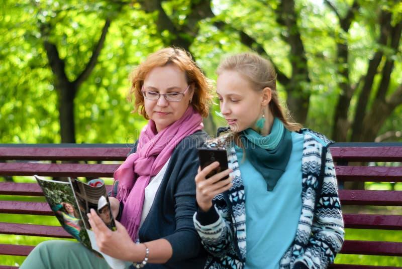 La maman et la fille ont lu un magazine en parc images stock