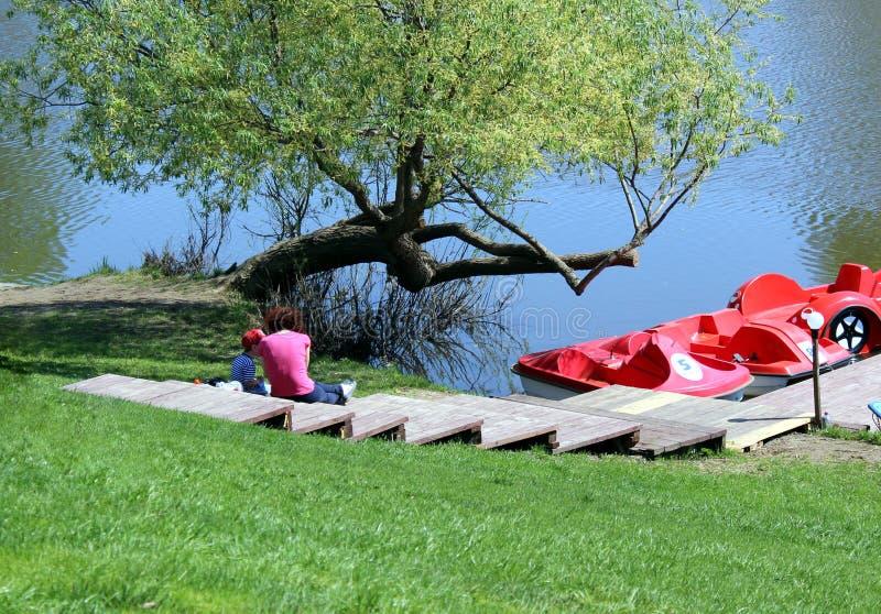 La maman et la fille s'asseyent sur la berge et le repos photos libres de droits