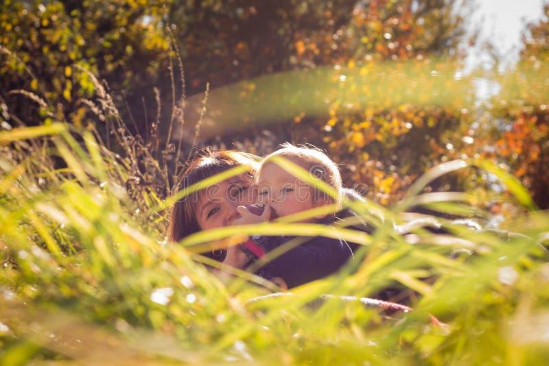 La maman et la fille se situent dans l'herbe dans la perspective des arbres d'automne images libres de droits