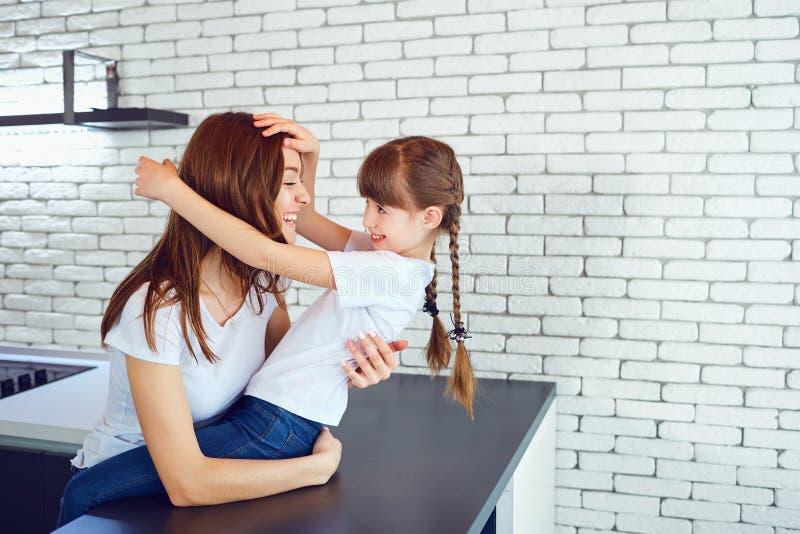 La maman et la fille sont sourire, jouant à l'intérieur image stock