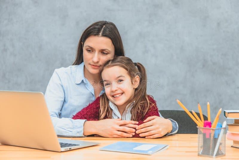 La maman et l'écolière s'asseyent à la table heureuse La maman a étreint sa fille et a plongé dans un ordinateur portable ?motion images libres de droits