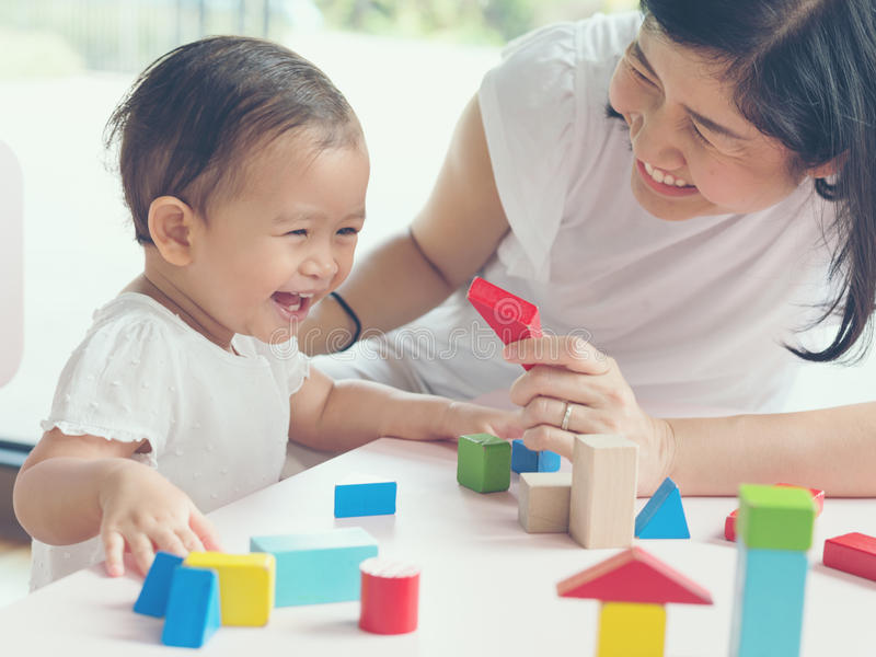 La maman et la fille asiatiques badinent jouer avec des blocs Effets de vintage et images libres de droits