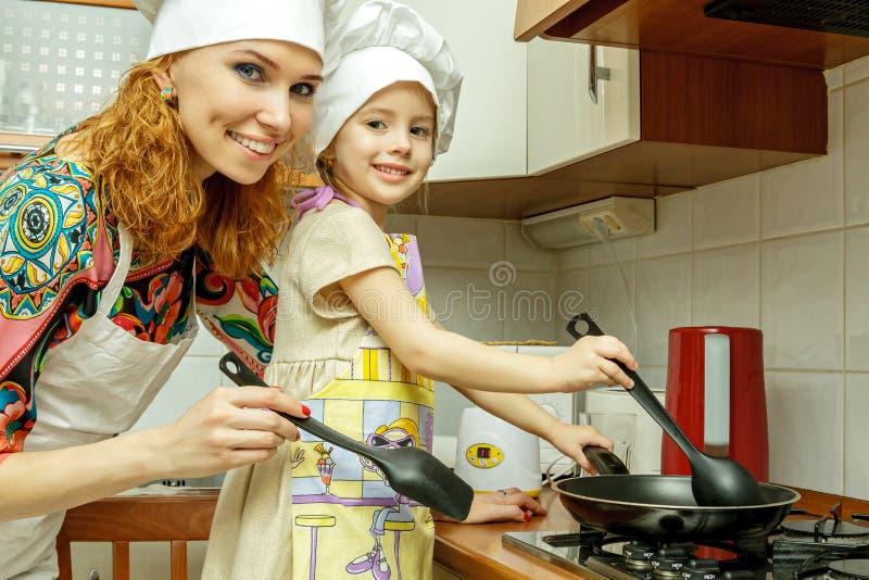 La maman et la fille dans des chapeaux blancs de chef font cuire dans la cuisine photo stock