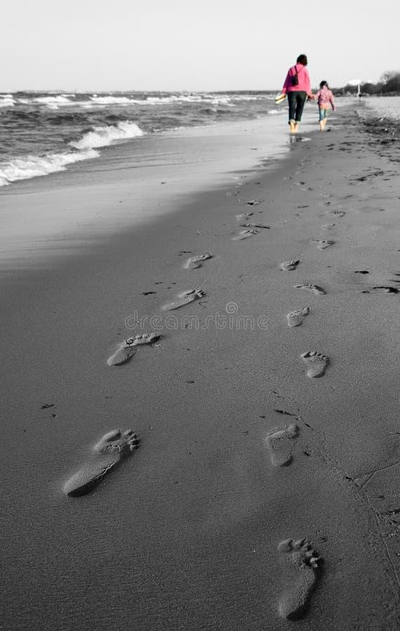 La maman et le descendant marchent - empreinte de pas dans la côte photo stock