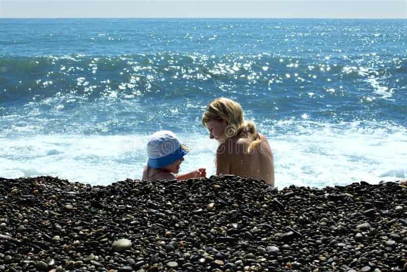 La maman et le fils au Panama bleu jouent dans le ressac près du pebbl humide photo libre de droits