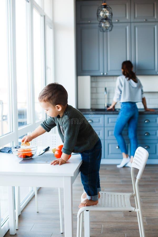 La maman et le fils préparent une salade dans leur cuisine images libres de droits