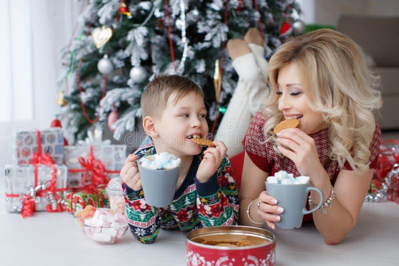 La maman et le fils se trouvent près de l'arbre de nouvelle année avec de grandes tasses de cappuccino et de guimauves image libre de droits