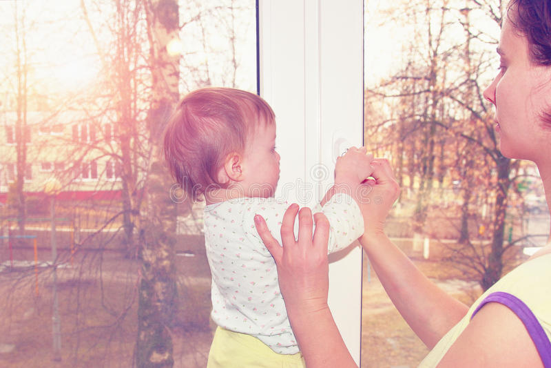 La maman et le petit bébé ferment la fenêtre avec une clé photo stock