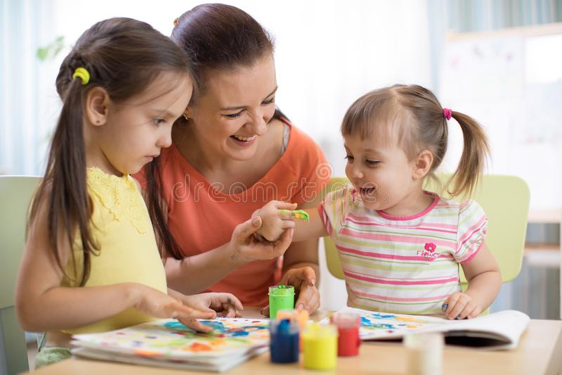 La maman et les enfants dessine avec les peintures colorées Les jeux avec l'affect d'enfant badine tôt le développement photo libre de droits