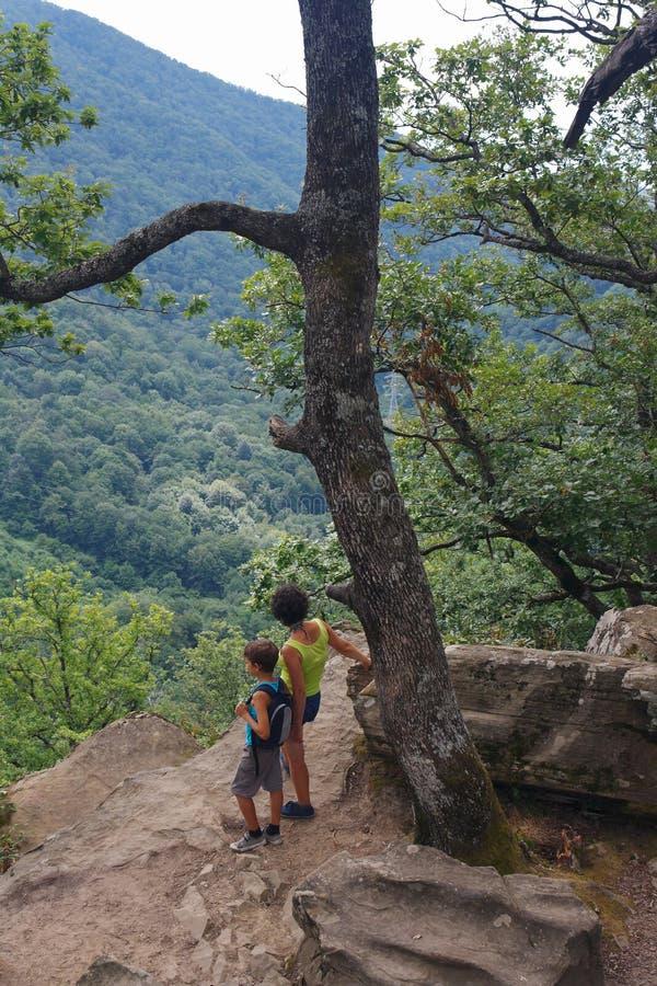 La maman et les petits touristes de fils regardent de la haute montagne pour regarder ci-dessous photos stock