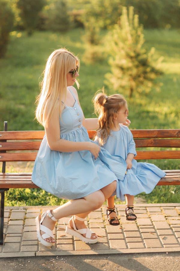 La maman et sa petite fille s'asseyent sur un banc en parc images libres de droits