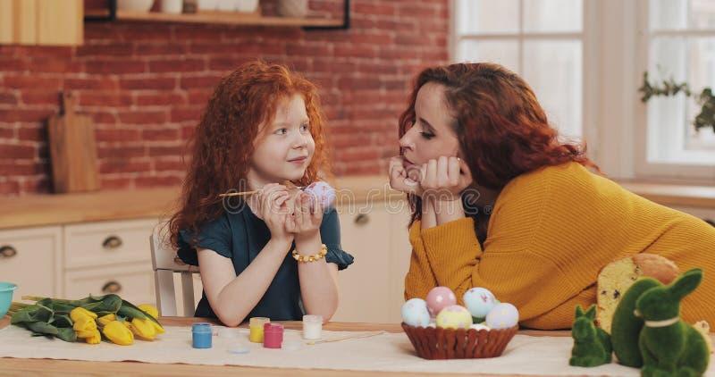 La maman et sa petite fille se préparent à Pâques Peu fille peignant des oeufs de pâques dans la cuisine confortable Mère de sour photo libre de droits