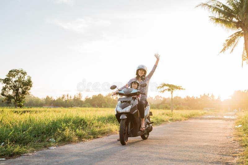 La maman et son enfant ont plaisir à monter le scooter de moto photo stock
