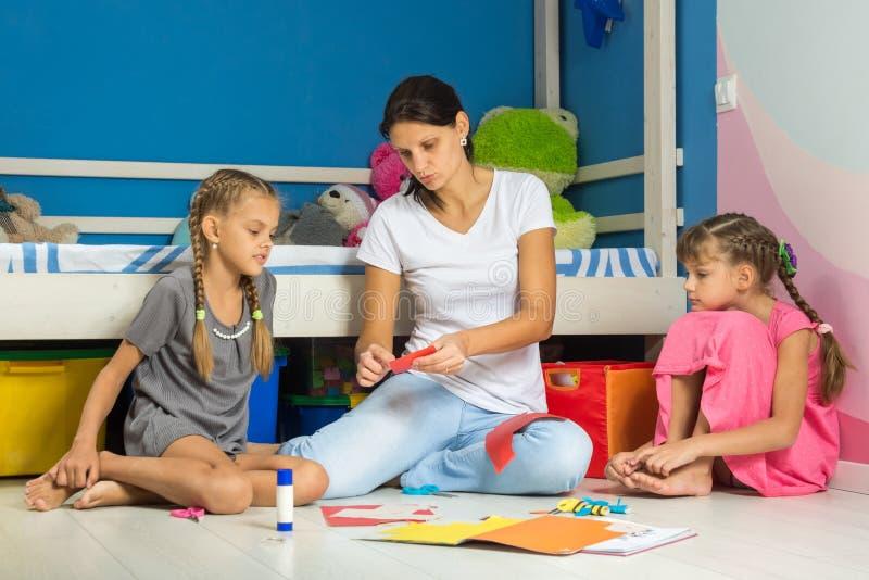 La maman explique des filles comment correctement couper des figures de papier coloré photos libres de droits