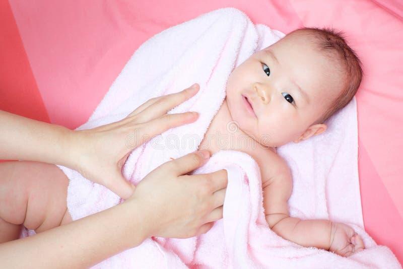 La maman frottent son bébé pour sécher photo stock