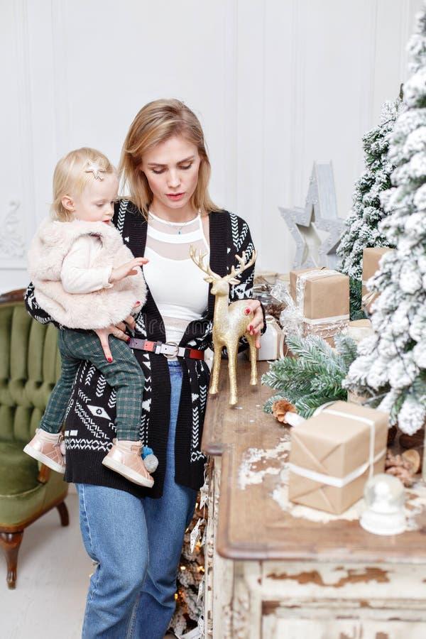 La maman gaie embrasse sa fille mignonne de bébé Parent et petit enfant ayant l'amusement près de l'arbre de Noël à l'intérieur a images libres de droits