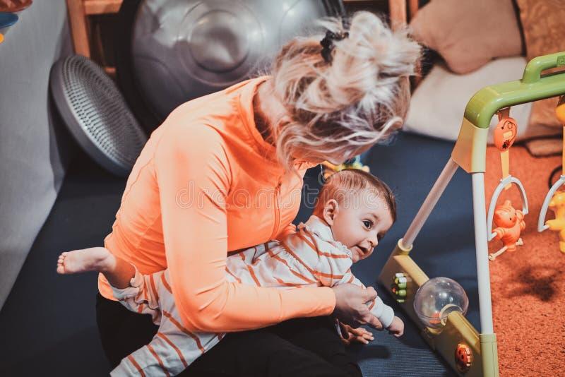 La maman gaie joue avec son bébé tout en attendant un docteur images stock