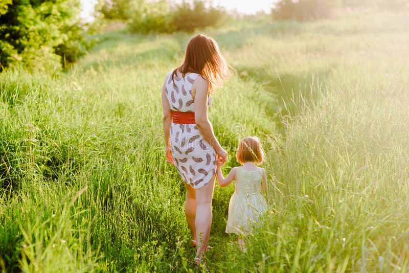 La maman garde la main de la fille et marche la promenade sur la nature dans la lumière de coucher du soleil photographie stock libre de droits