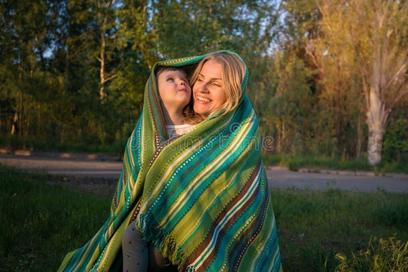 La maman joyeuse étreint avec leur petite fille drôle en parc images libres de droits
