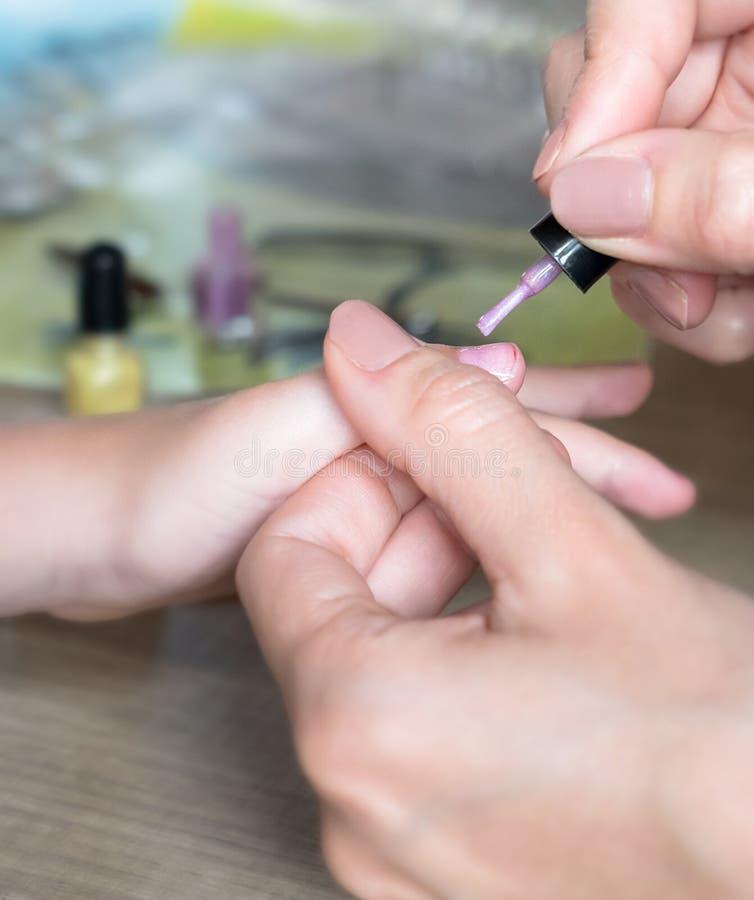 La maman peint des ongles du ` s de fille sur des mains avec le vernis à ongles rose sur merci photos libres de droits