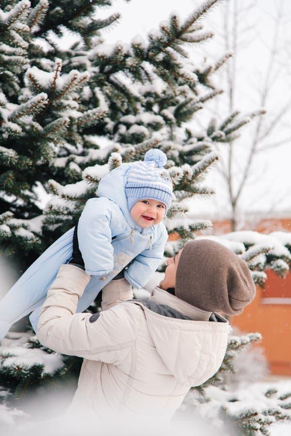 La maman près de la neige a couvert des jeux d'arbre de Noël de bab images stock