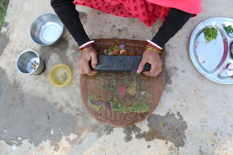 La maman prépare le chutney avec les outils traditionnels image libre de droits