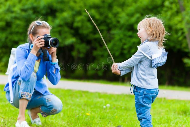 La maman prend l'enfant de garçon de photos en parc en été photos libres de droits