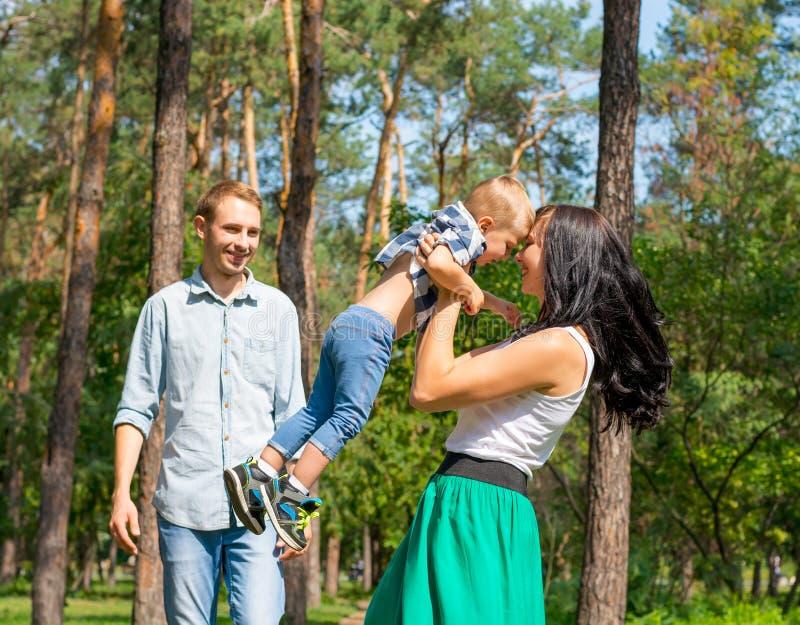 La maman a pris son fils et l'a tourné autour Le papa se tient à côté de photographie stock libre de droits