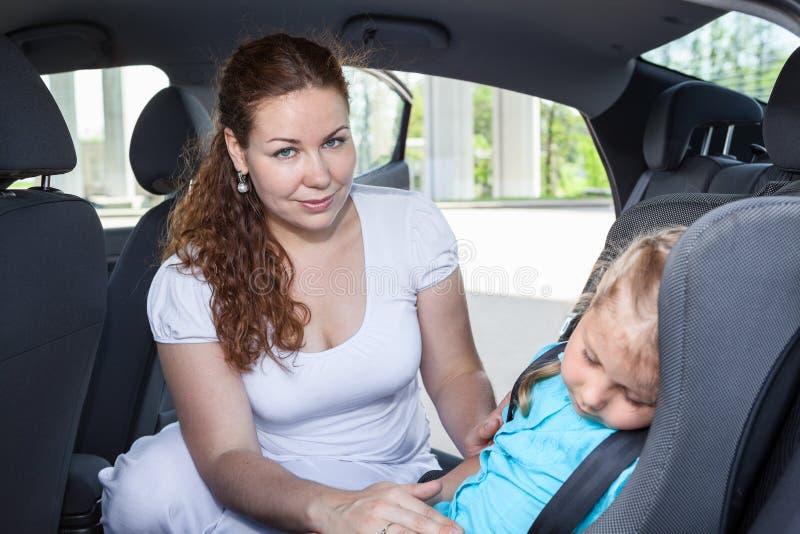 La maman réveille la fille de sommeil dans une voiture photos stock