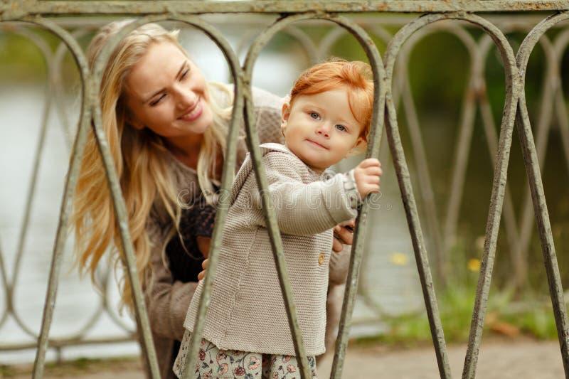 La maman regarde le bébé roux et rire, automne image libre de droits