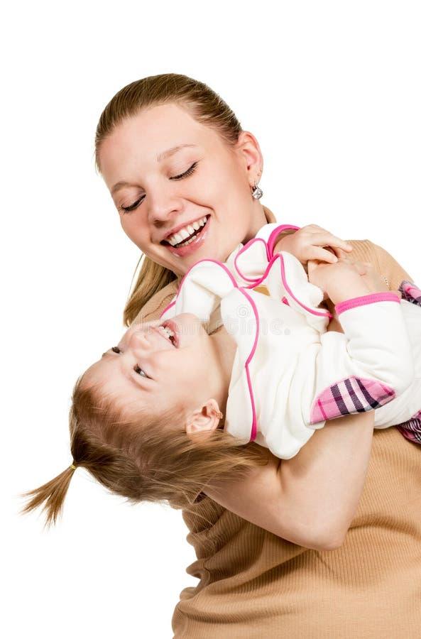 La maman tient l'enfant dans des ses bras et joue image stock