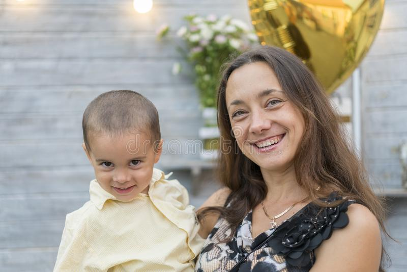 La maman tient un enfant dans des ses bras Une famille heureuse Jeune mère tenant son bébé dans des ses bras et frotté mon mother photos libres de droits