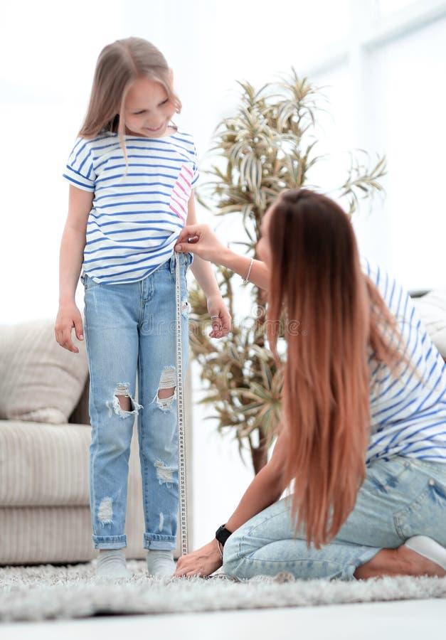 La maman vérifie la longueur des jeans de sa fille image libre de droits