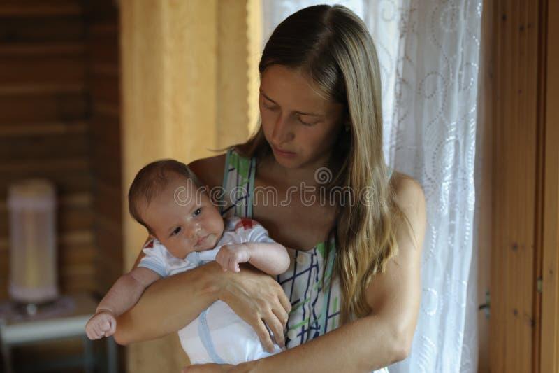 La mamma abbraccia il suo bambino nelle sue armi fotografie stock