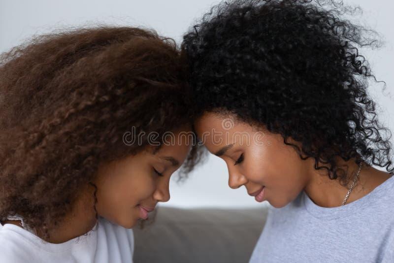 La mamma afroamericana e la figlia hanno insieme momento vicino immagini stock libere da diritti
