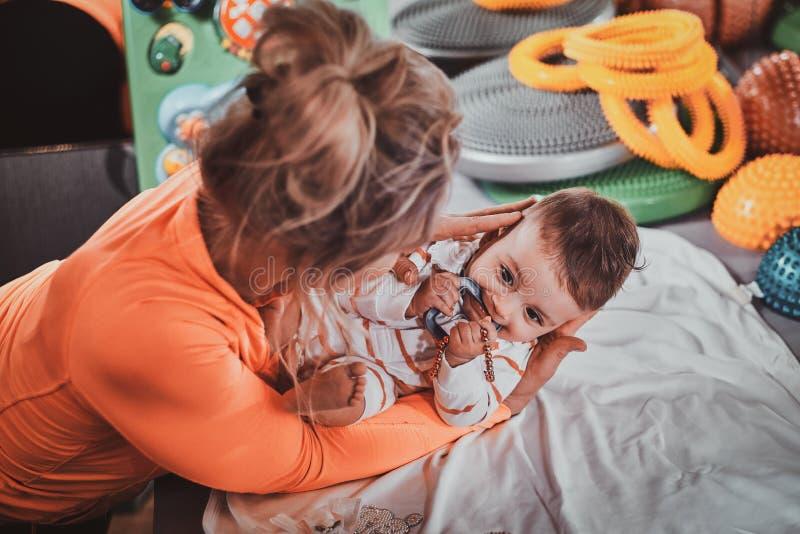 La mamma allegra plaing con il suo neonato al gabinetto del massaggiatore fotografia stock libera da diritti