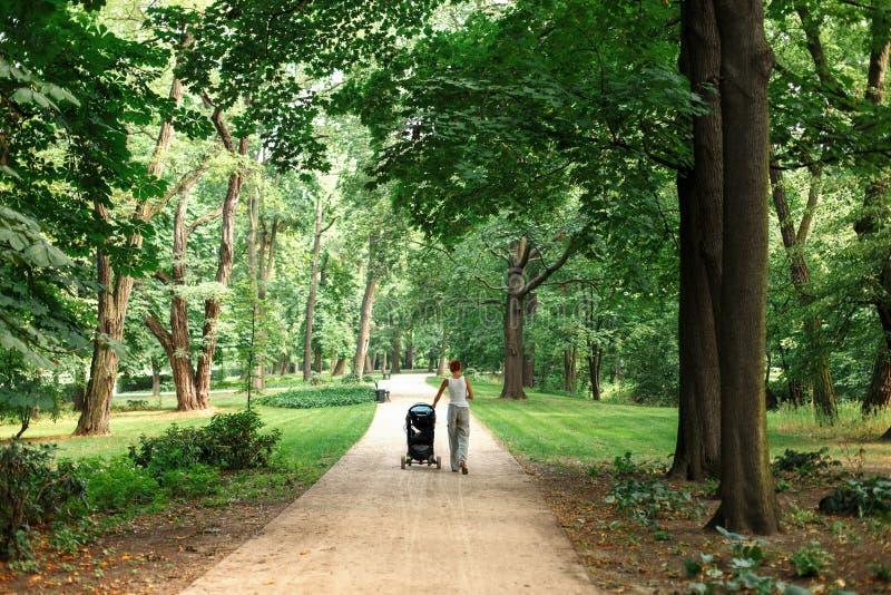 La mamma cammina nel parco con il passeggiatore immagine stock libera da diritti