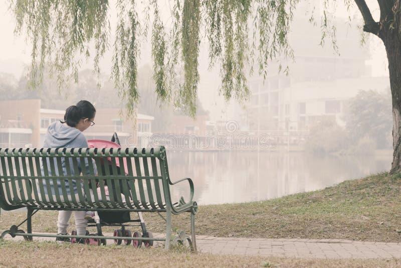 La mamma cinese ciao il bambino nel carseat del bambino fotografie stock libere da diritti