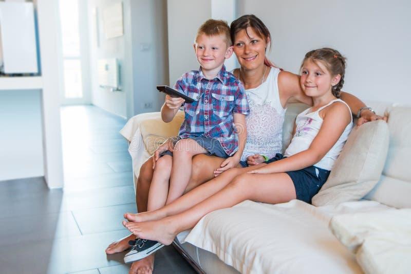 La mamma con i suoi bambini sta sedendosi sul sofà a casa Un bambino cambia il canale televisivo con il telecomando immagini stock libere da diritti